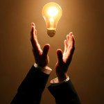 Горящая лампочка между руками