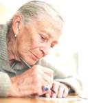 Пожилая женщина подписывает бумаги